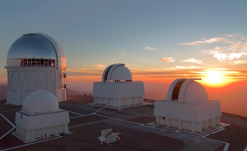Las cúpulas de los telescopios en el Observatorio Interamericano de Cerro Tololo en Chile abren sus compuertas en preparación para una noche de observación, mientras se pone el sol. Crédito: T. Abbott y NOAO/AURA/NSF - Diario Puerto Varas